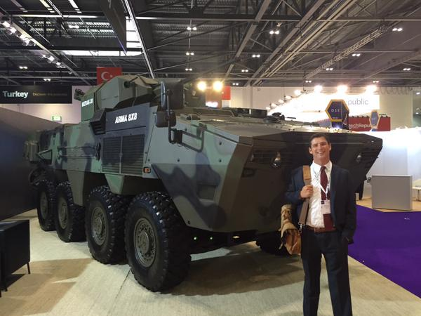 Avascent Analytics Product Manager Keith Arscott stands with an Otokar Armored Vehicle at DSEI 2015